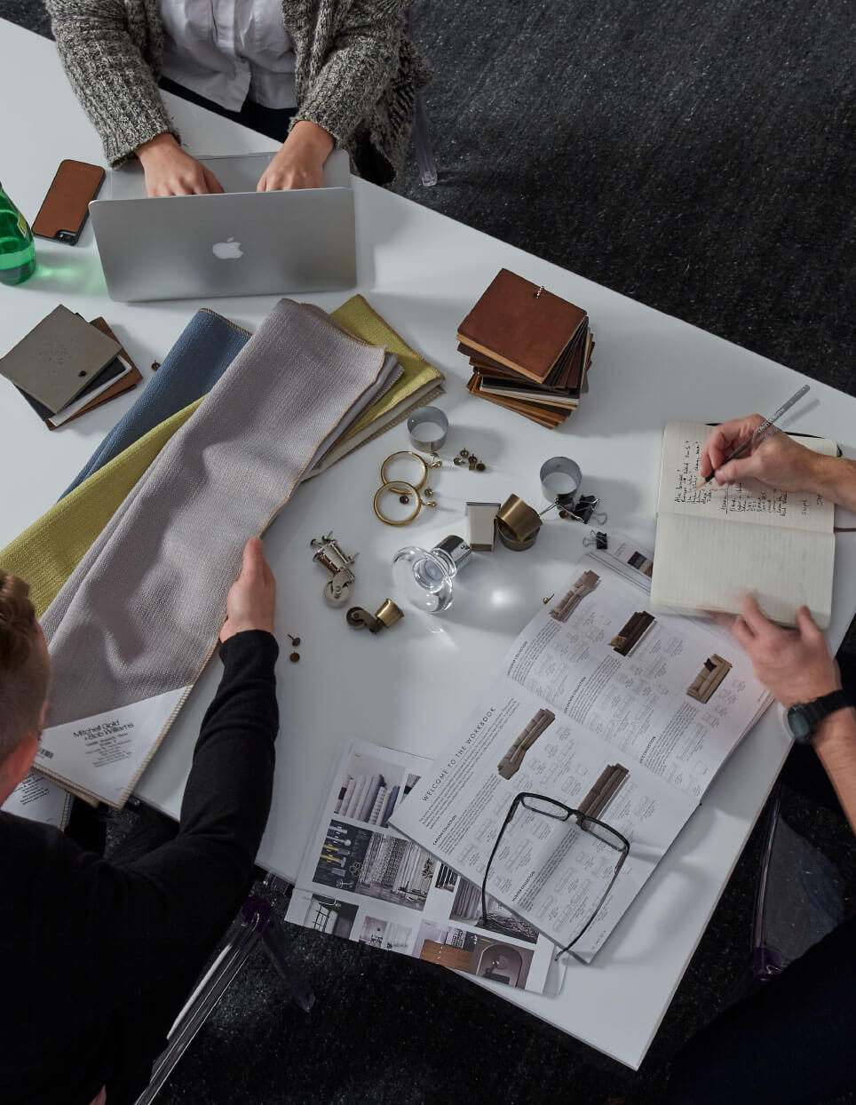 People looking at fabric options and other swatches for in-home design